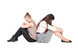 Upset girls sitting back to back